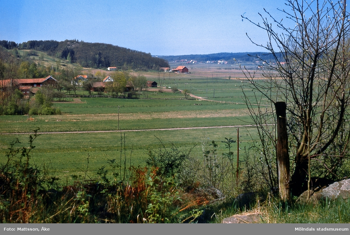I förgrunden ses några av gårdarna i Kärra, Mölndal, på 1960-talet. Ett stycke längre bort, i mitten, ses gården Bunketorp. ÅM 6:10.
