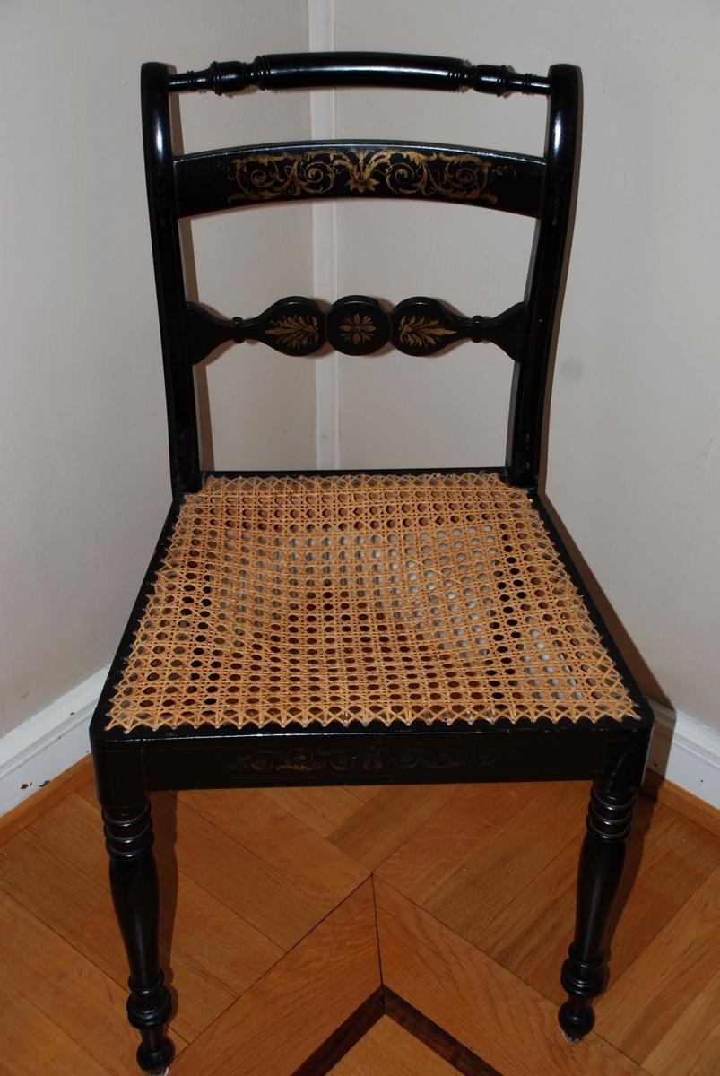 Sen Sheraton-type, ca. 1810, sortlakkert med gull. Dreiete ben, rett sarg med avrundete hjørner. Bakbeina firkantet, bakutgående. Ryggstavene svakt s-formet, ender i små bakovergående ruller, forbunnet med en dreiet, konkav stav - som utgjør toppstykket. Derunder et glatt stykke, noe oppadbuet og konkavt. Mellom dette og setet er det et vertikalt skåret brett med en sirkel i midten, hvorfra der går to løkformete plater - en fra hver side.  Sjablongmessig gullornamentikk (ant. imitasjon av lys intarsia på ibenholt) - ranker i klassisk manér, samt palmett og stjerner, anbragt på sargen og de nederste ryggbrett. Dertil linjeførte røde streker - på intarsia-manér.