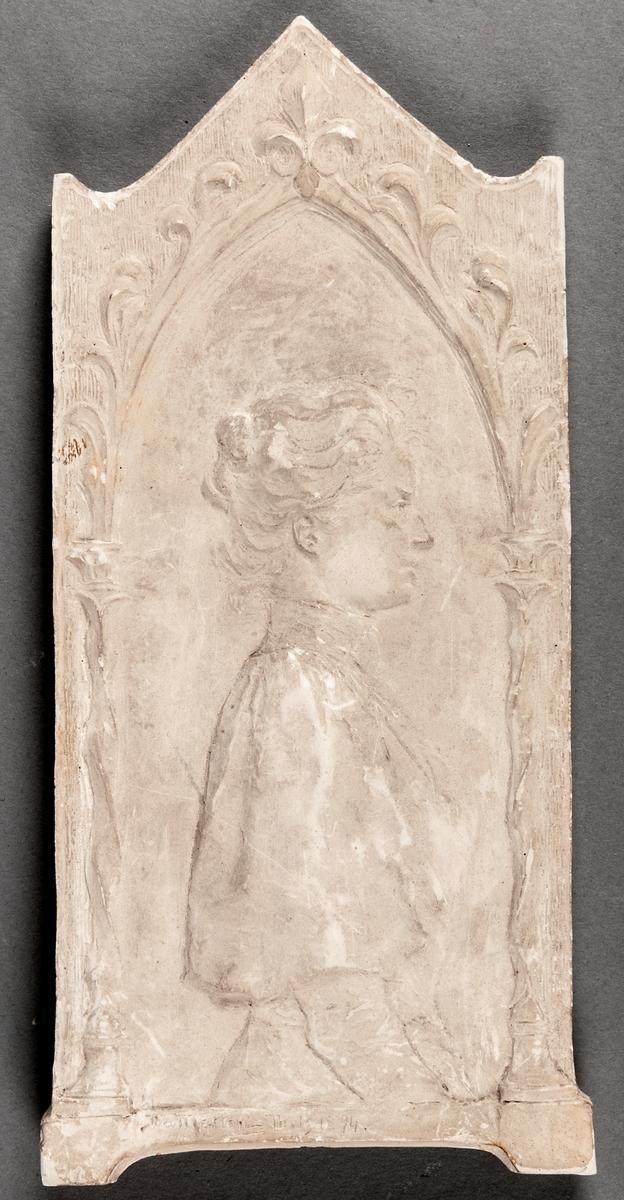 Gipsrelief föreställande kvinna i profil. Omgivande dekor i nyrennässansstil. Signerad Ida Matton Paris 1894.