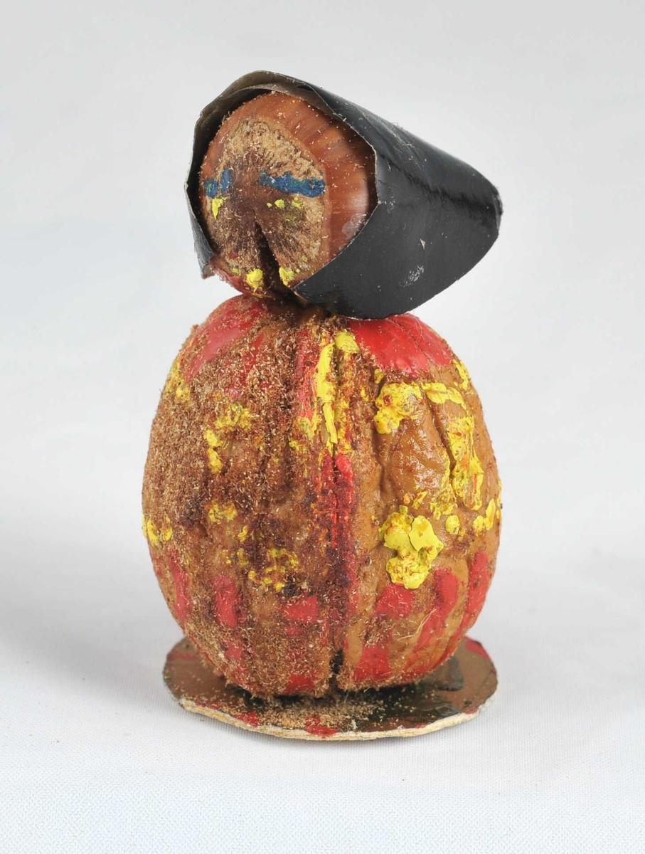 Heimelaga figur, truleg nissekone. Hovudet er ei hasselnøtt med måla fjes. Skaut av glanspapir.Kroppen er ei valnøtt som er dekorera med måling slik at det ser ut som ei kappe eller kåpe. Figuren står på ei sirkelforma, gullfarga papplate.