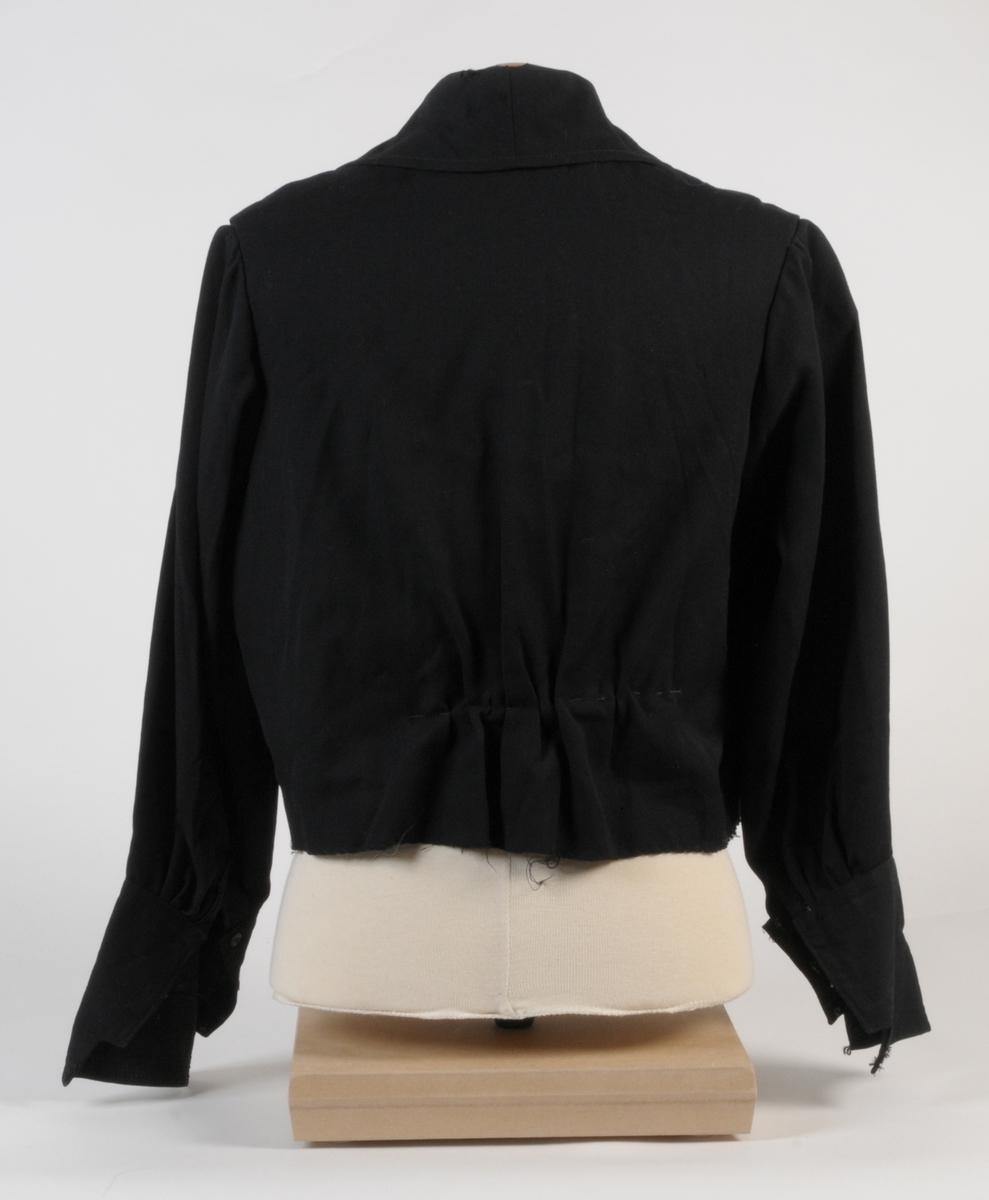 Damblus av svart ylletyg med randigt bomullsfoder i beiget och vitt. Blusen har krage och uppslag på ärmarna samt dekoration av pärlbroderi på tyll över framstyckena. Plagget knäpps med tryckknappar mitt fram.