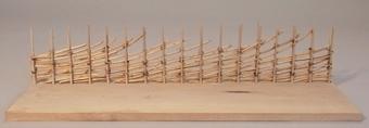 Miniatyrmodell av fastbandshage, står på träskiva.