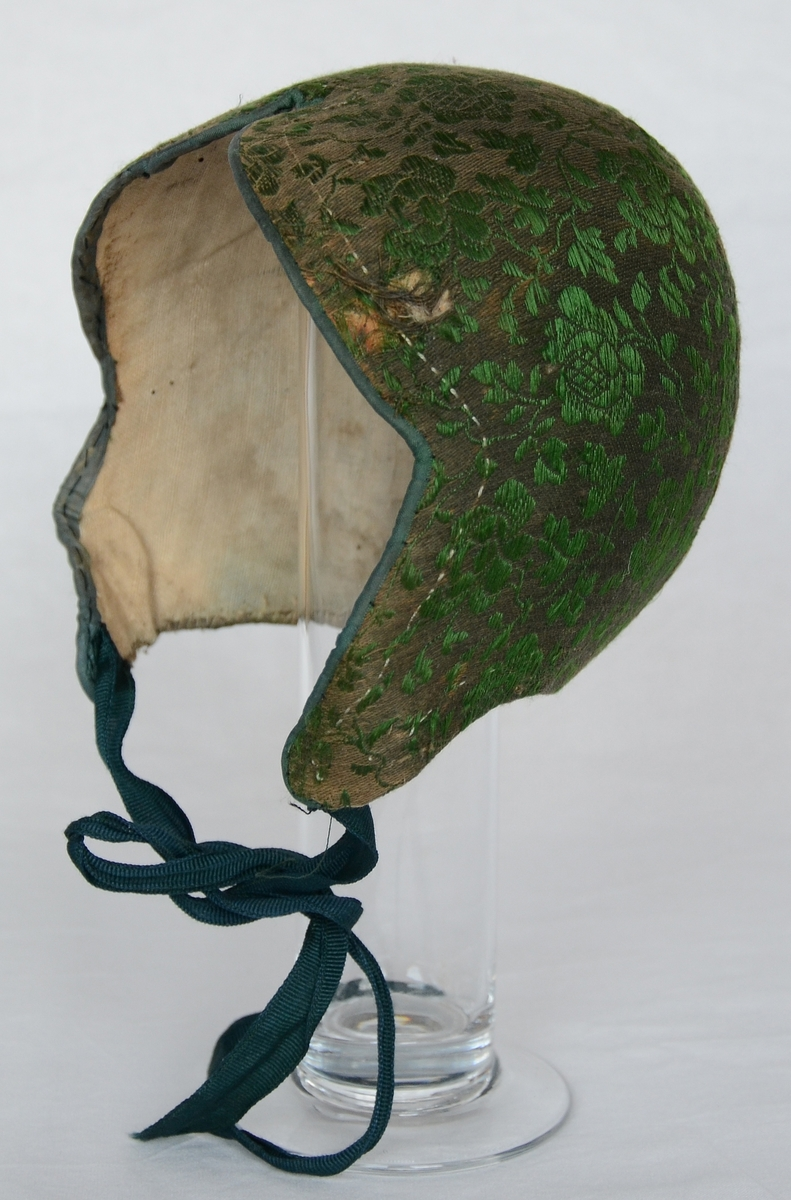 Bindmössa, så kallad finka, klädd med mönstervävt bomullstyg i brunt med blommor i grönt silke. Knytband av grön sidenrips. Fodrad med linnelärft.