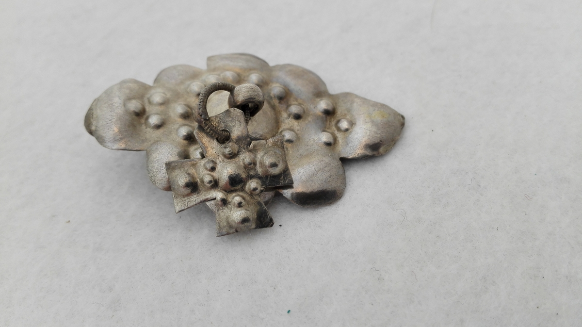 Form: Utpoklet sølvplate med korsforma lauv.