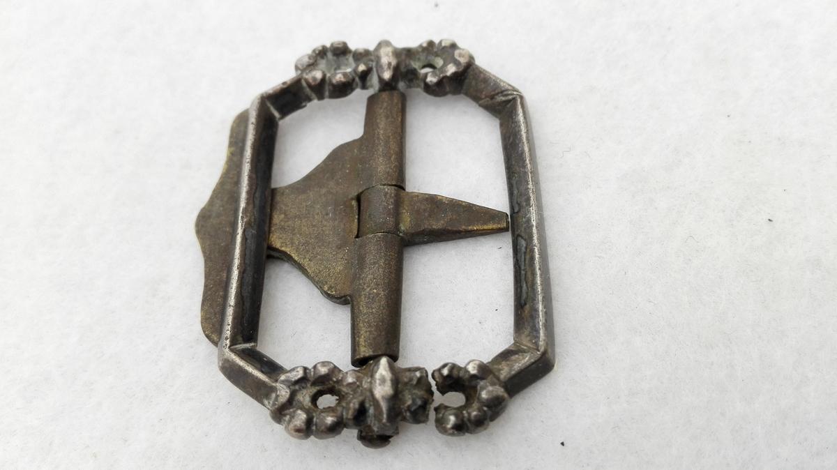 Form: Avlang 1 knæspende av sølv.  Avlang knæspende av sølv. Langsiderne rette med brudte hjørner, trekantet tverrsnitt. Paa begge kortsider en kringleformet sløife. Tanden av messing. Paa baksiden stemplerne  P. 18 (?) 01. M.P. (Guldsmed i Bergen Mathias Pettersen, f.1762 d. 1812) Kjøpt av L. J. Berdal, Feios.