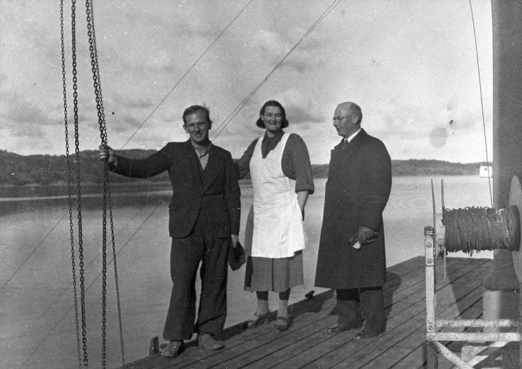 """Enligt uppgift: """"Fotografi år 1941 från övre bryggan vid stationsbyggnaden. På bilden syns från vänster Oscar Åkermo, Jenny Fagerberg (husmor på stationen) och August Nilsson (trålmästare)""""."""