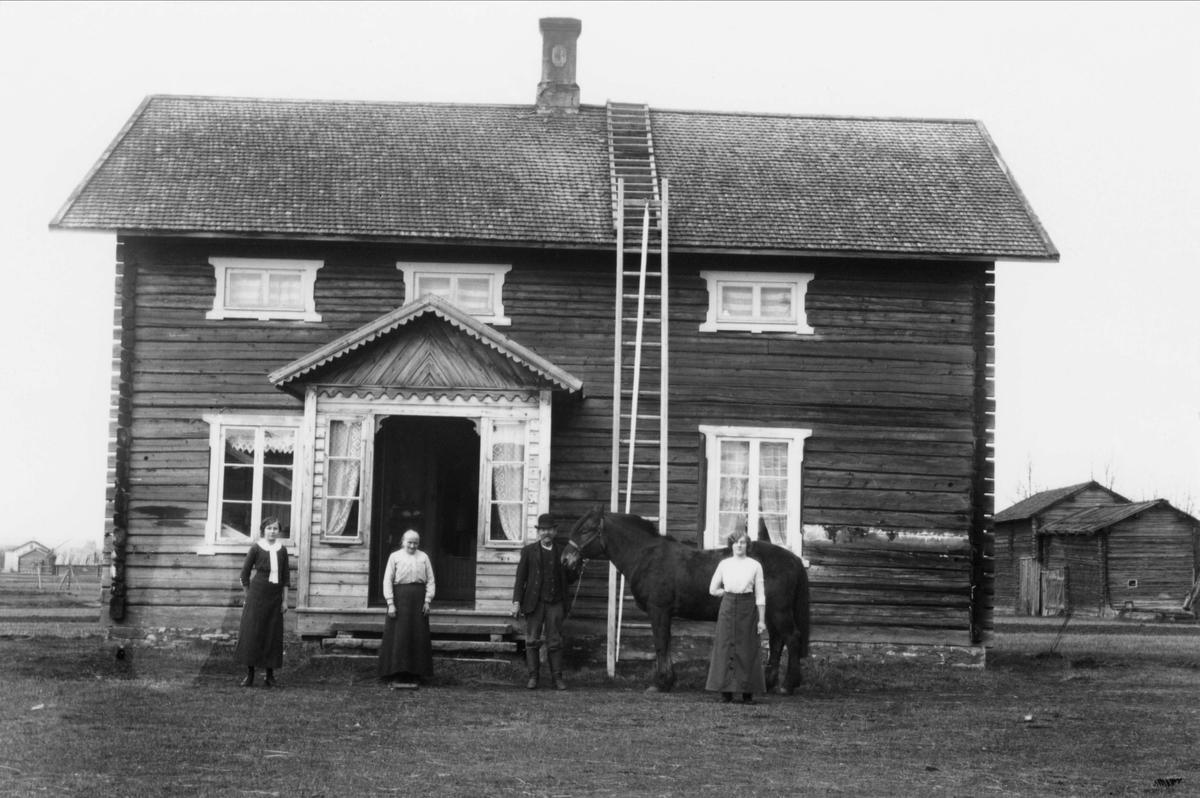Tre kvinnor, en man med häst utanför bostadshus