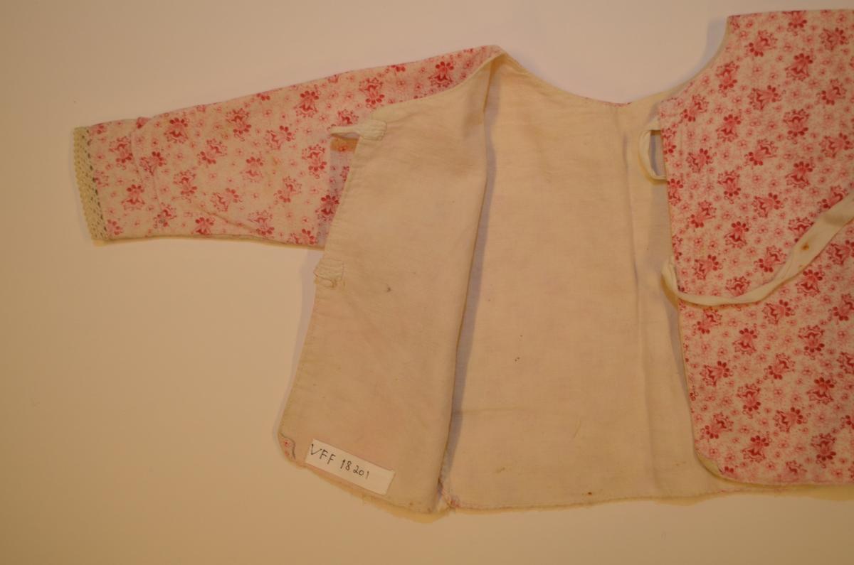 Spebarns-trøye i kvit bomullsflanell med trykt blomstermønster i raudrosa. Fóra med kvit bomull. Opning i ryggen med to sett knyteband. Bomullsblonde i ermekantingane. Maskinsydd, kasta over med hand. Klypt i eitt stykke.