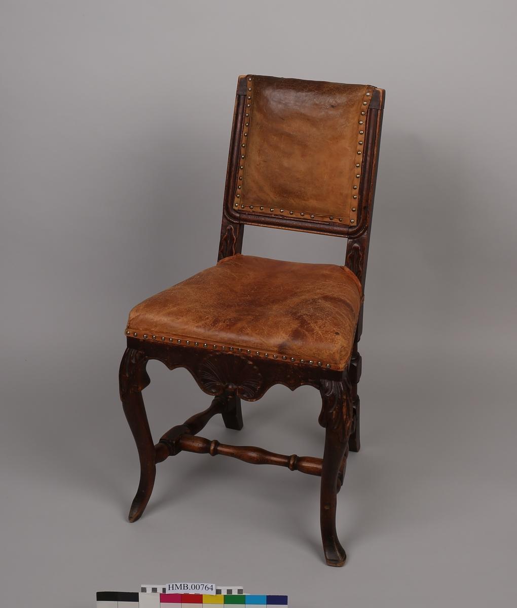 Høyrygget stol med skinntrekk.