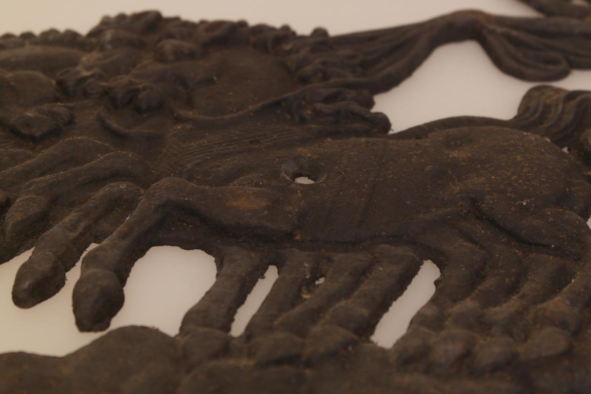Ovnsrelieff i støpt jern. Relieffet forestiller en gudinne i en romersk stridsvogn trukket av et firspann. To utsparinger (i en av hestene og i vognen), antakelig for skrue.