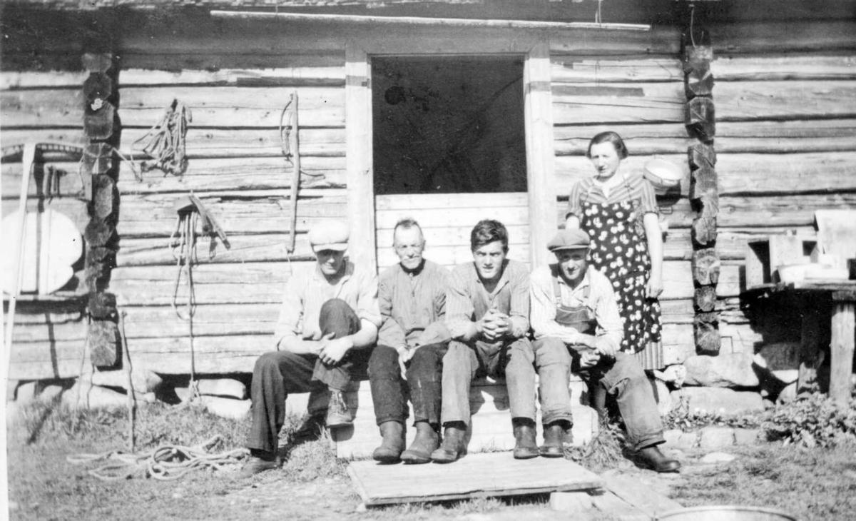 Repro: Seterliv:  Fire menn (slåttekarer?) og en kvinne utenfor seterhus. På veggen forskjellig innhøstningsredskaper og osteform.