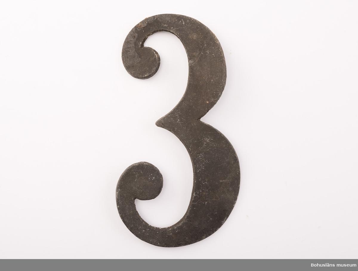 1 psalmnummersiffra  av bly, höjd 10.5 cm, 3. UM005660:054.  Ur handskrivna katalogen 1957-1958: Trälåda m. siffror för psalmnummer 1-8: Bly. H.: 16 cm, m. utsirningar 9-19: Bly. H.: 9 à 10 cm; m. utsirningar. 20-28: Bly o mässing. H.: 15 cm. 29-31 Bly H.: 13 cm. 32-42: Bly o mässing. H.: 10 cm. 43-51: Bly o mässing. H.: 7 cm. 52-54: Gjutna av gulmetall. H.: 10 cm. 55-56: Vitmålad järnplåt. 57: Bly. H.: 10,5 cm.  Lappkatalog: 13