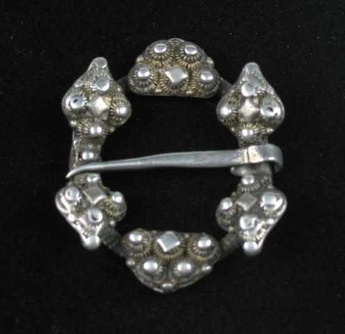 """Hornring i sølv med ring av skruetråd.. Stolpene (hornene) har hjerteformede ender. Hvert """"hjerte"""" har fire doble perlekruser med en dobbel plate i midten. I krusehjørnene er det små perler som fyllmotiv. Mellom stolpene er det en segmentformet kruseplate med doble perlekruser og en diamant. Også her er små perler brukt som fyll i krusehjørnene. Hornene og platene er på undersiden forsterket med sterke ribber. Tornen har v-formet strekdekor."""