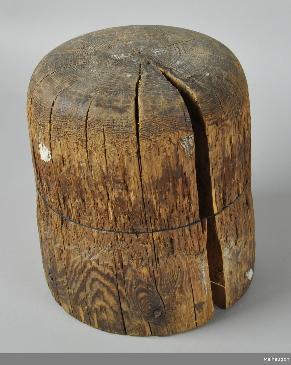 Hatteblokk skåret ut av ett trestykke. Hatteblokken har en sylinderform hvor toppen er avrundet. Treverket er meget oppsprukket.