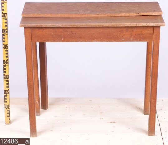Anmärkningar: Spelbord. sengustaviansk modell, 1800-tal.  Bordsskiva bestående av två delar som är fästa i varandra med gångjärn. Skivan kan vikas ihop och fällas ut. En draglåda med spår av bläck inuti (bild 12486__b). Fem fyrkantiga ben med räffelliknande dekor i kanterna. Benet som sitter längs den ena långsidan går att dra ut och därpå kan man lägga den ena halvan av bordsskivan. Bild 12486__c visar bordet då benet och bordsskivan är fullt utfällda. H:755 L:840 Dj:410  Hela bordet är av ek utom vissa delar av lådan och vissa delar av innanmätet av själva bordet som är av furu.  Tillstånd: En fjärdedel av bordsskivan saknas. Jämt slitage över hela bordet.