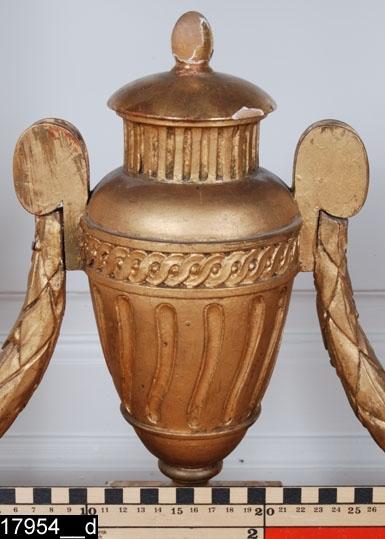 """Anmärkningar: Konsolbord (spegelbord), gustavianskt, omkring 1780.  Löstagbar halvmåneformad marmorskiva som är profilerad i kanterna. Sarg med skurna dekorer. Under sargen hänger festonger (bild 17954__b). Fyra nedåt avsmalnande ben med skurna dekorer, bland annat bladstavar, rosettanfanger längst ned och fotavslutningar i pinjekotteform (bild 17954__c). Ett fotkryss förbinder benen. På fotkrysset finns urna med skurna dekorer, bland annat en runtgående bandfläta (bild 17954__d). H:865 L:1150 Dj:580  Tillstånd: Skivan är sannolikt senare (den är släthuggen undertill). Skivan är spräckt och lagad. Underredet är delvis omförgyllt. På sargens insida finns en blyertsanteckning som lyder """"Förgyllaren Gustaf Andersson Westerås 1897"""".  Historik: Gåva från Fröken Eva Karlssons, Västerås, dödsbo 1974 enligt testamente.  Utdeponerad till landshövdingens residensvåning i Västerås slott 1981-06-18."""