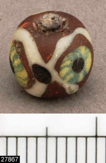 """Anmärkningar: Badelunda sn, Tuna undersökt 1952-1953 Pärla, från båtgrav daterad till yngre järnålder, 850 e.Kr. (Vikingatid)  Pärla, från grav 75. Mosaikpärla, brun med vita linjer och 3 stycken gula  """"ögon"""" med gröna linjer och svart punkt. Funnen i klumpen bestående av fyndnr 124,144,145. Diam 9 mm.  Pärlan är onumrerad - utan fyndnummer - och finns inte upptagen i rapportens fyndförteckning. Pärlan var tidigare felaktigt omregistrerad under invnr 28010, numera återförd till det mer ursprungliga invnr 27867. Enligt en tidigare registrering bestod posten av 3 stycken pärlor, vilket troligen var en feltolkning av texten i fyndasken - då det står: """"Fr. klumpen 124 -144-145. Mosaikpärla, brun med vita linjer och """"ögon"""", 3 st, gula med gröna linjer och svart punkt (onumrerad) """".  Litteratur Nylén, E. & Schönbäck, B. 1994. Tuna i Badelunda. Guld kvinnor båtar I. Västerås kulturnämnds skriftserie 27. Västerås. s 44ff. Nylén, E. & Schönbäck, B. 1994. Tuna i Badelunda. Guld kvinnor båtar II. Västerås kulturnämnds skriftserie 30. Västerås. s 112 ff, 150ff, 200.  Fotograferad teckning negnr A-7422"""