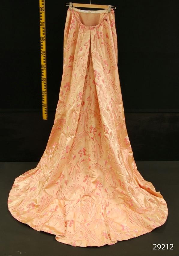 """Anmärkningar: Irsta sn Gäddeholm Använd av Ewa Lewenhaupt född Beck Friis 1858 - 1940.  Tvådelad klänning, blus och kjol, av laxrosa brokad med vita och skära mönster. Midjekort överdel dekorerad med små rynkade band och extra puffar på ärmarna, liksom i urringningen av rosa chiffong. Insydd korsett av bomull med stålvajrar i både ryggen och framstyckena. Överdelen knäpps med 12 hakar och hyskor på framsidan. Urringningen är över crepe georgetten försedd med ett rynkat parti av rosa chiffong. Framstyckena är även dekorerade med två stora blommor sydda av samma brokadtyg som klänningen i övrigt. En är placerad under höger axel och en i midjan på vänster sida. Märkt Augusta Lundin Stockholm på band i klänningens överdel. Vid kjol med släp och tornyr bak. Två sydda sjupa veck på framsidan av kjolen. Runt kanten i jämnhöjd med längden framtill en smal volang av rosa satin med vågklippt nederkant, bredd 50 mm. Kjolens totala längd 1650 mm. Kjolen märkt med bomullsband """"nr 8""""."""