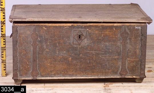 Anmärkningar: Kista, omkring 1800.  Gångjärnsförsett platt lock med hörnbeslag. Järnhandtag på kortsidorna. På framsidan finns en nyckelskylt med genombruten dekor, bl.a. i form av hjärtan (bild 3034__b). Invändigt är kistan tom, där finns spår av en läddika längst till vänster (som saknas), bild 3034__c. Insidan av locket är orange-rött målat. Utvändigt är hela kistan brunmålad och bär spår av naturligt slitage. Två konturerade medliknande brädor fungerar som fötter på kortsidorna. H:495 L:1010 Dj:615  Följande är en äldre registrering gjord av f.d. föremålsantikvarie Roy G. Cassé: På Vallby Friluftsmuseum finns en tallrik dubbelmärkt med detta nummer. I samband med stiftelseupplösningen 2005 gjordes ett urval, och resterande överfördes i Västerås stads ägo att förvaltas av Vallby Friluftsmuseum. Tallriken är en av de föremål som överlåtits.  Tillstånd: Ett beslag saknas på locket, de övriga är skadade. Nyckelskylten på framsidan är skadad. Nyckel saknas.  Historik: Inköpt genom Nils Nygren på auktion på Karlslund 1924.