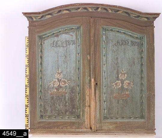 """Anmärkningar: Skänkskåp (överdel), målad datering 1848.  Framskjutande rundat krön med grönvit bladbård. Spegelförsedda pardörrar med gerade och profilerade lister. Speglarna är försedda med rosmåleri och stiliserad grönvit bladbård som omger dem (närmare detalj på måleriet på höger dörr, bild 4549__b). Höger dörr har också en nyckelskylt i järn. På vänster dörr står det """"L.E.S. 1848"""" och på vänster dörr står det """"A.P.D. 1848"""" (båda är ägarmonogram). Färgen på dörrarna bär spår av naturligt slitage. Invändigt en skedhylla samt tre hyllor med profiler längst ut på kanten. Lås i järn på höger innerdörr. Hank i järn på vänster innerdörr och tillhörande hankfäste på det översta hyllplanet. Sidorna på skåpet har olikartade målningar. Vänster sida har samma färg som den bruna färgen på framsidan, medan den högra sidan är grön och brun. Profilerad list längst ned. H:1300 Br:1340 Dj:470  Måleriet på detta skåp är intressant ur flera synvinklar. Måleriet uppvisar stora likheter med måleriet på skåpen med inv. nr. 4847 (dat. 1844) och 4836 (dat. 1835). Med största sannolikhet rör det sig om samma målare. Tre saker talar för detta. För det första är skåpen målade inom ett rimligt tidsintervall, vilket visar att en och samma målare kan ha utfört det under sin levnad. För det andra antyder proveniensen i två fall (Himmeta och Munktorp socknar) att målaren rört sig inom ett rimligt geografiskt avgränsat område. Om förhållandet varit det motsatta - att måleriet påträffats på stora avstånd hade man varit tvungen att fråga sig om det inte kan röra sig om olika målare. För det tredje överensstämmer, som påpekats, måleriet på skåpen stilistiskt. På samtliga skåp har målaren målat en blomkomposition med tre rödvita rosor och svartvita blad som sticker ut på ett sätt som ger ett flammande intryck. I krönen på skåpen är en bladbård målad i svarta och vita färger. Även bladens utformning är gemensam för de tre skåpen. Det är högst sannolikt att målaren kommer från Västmanland eftersom ing"""