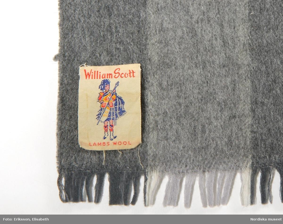 Halsduk, 1962-1968, av rutig, varp av vitt och två nyanser grått ullgarn. Inslag av grått, grönt, vitt och svart ullgarn, kort frans, text på påsydd etikett 'Wiliam Scott Lambs Wool'.