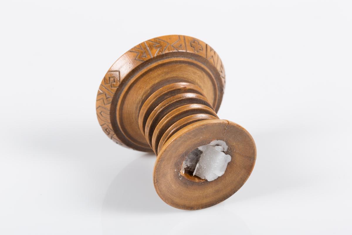 Lysestake i dreid tre. Lysestaken har rund form med en bredere rund fot. Rundt foten er det risset inn latinsk tekst (Ved kors til lys).