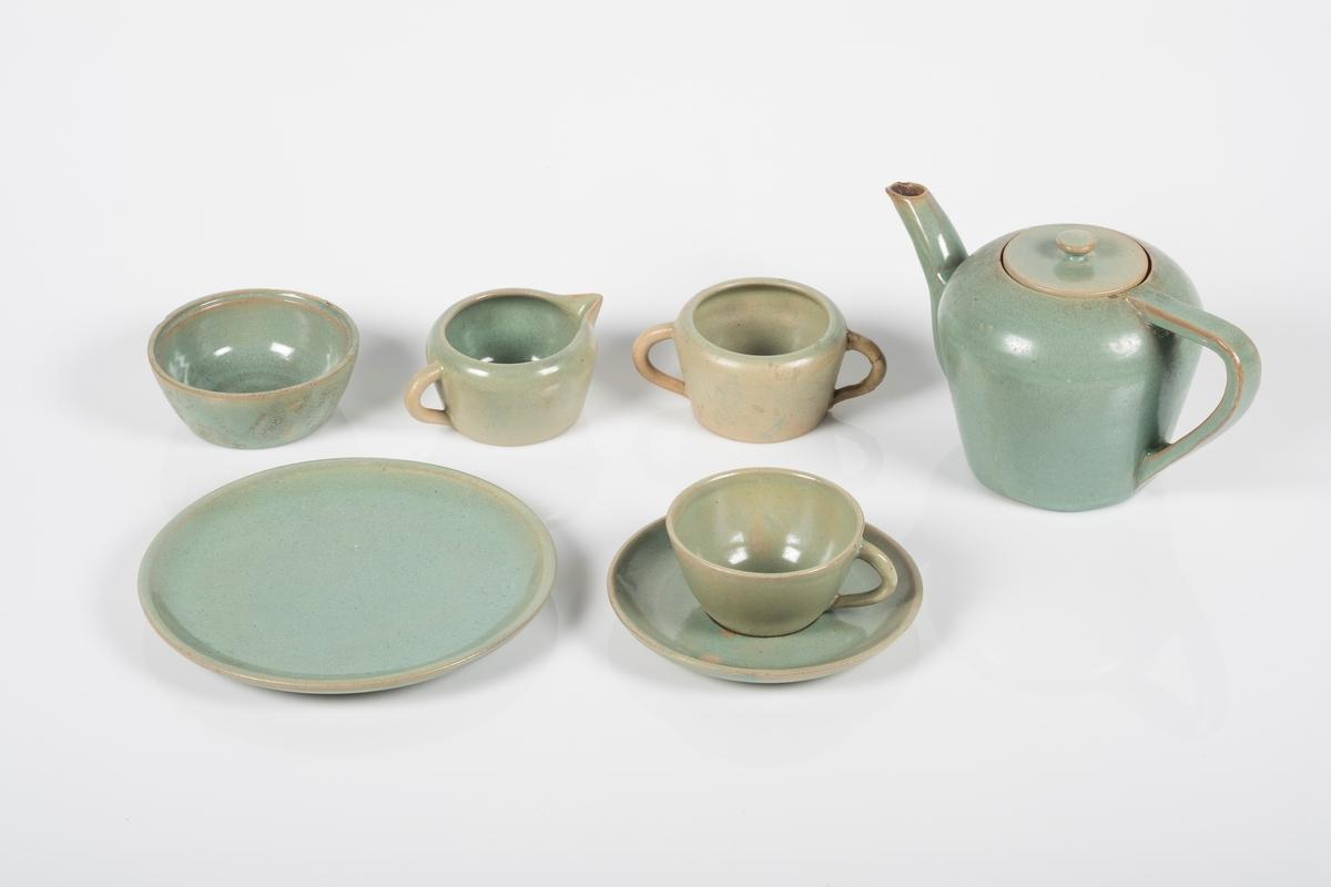 Teservise i keramikk med grønn lasur.  Settet består av 22 deler; 1 tekanne, 6 kopper med 6 skåler, 6 tallerkner (asjetter), 1 fløtemugge, 1 sukkerkopp og 1 skål. Grinisymbolet på bunnen av tekannen.
