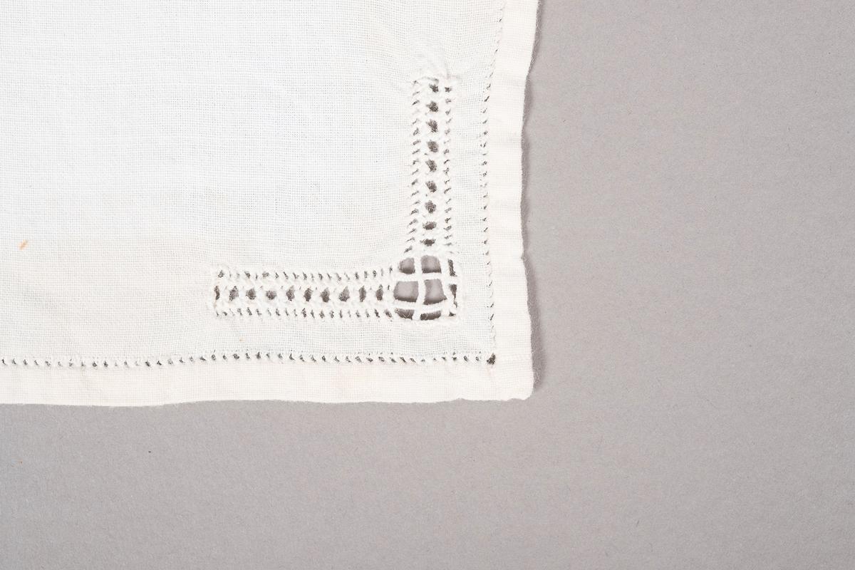 Hvit lommetørkle i bomull med hullbroderier, noen små brune flekker og spor etter nåler.