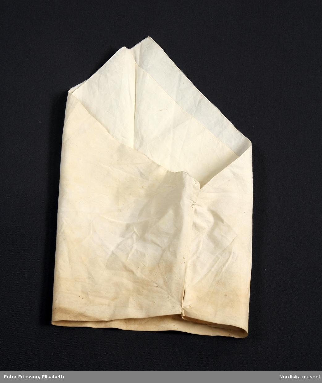 Hel kvinnodräkt A-I A. Kjol med liv B. Tröja, bindtröja C. Överdel D. Förkläde E. Huvudbonad F. Bälte G. 2 st pungtrossar H. Ett par handskar I. Bokkläde  E. Överdel,  längd 27 cm, ärmlängd 51 cm, kragbredd 8 cm.  Kort modell av vit tunn bomullslärft, öppen fram, bål i ett stycke med sidsömmar, helfodrad med linnelärft, vidsydda ärmar rynkade mot ärmlinning med sprund med hake och hyska. Ärmlinningen kantad med en smal maskinvävd spets som även sitter kring framkanterna och i kragens framkanter. Plattsömsbroderi på ärmlinning och  krage med vitt lingarn. Som applikation på framstyckena knypplad Vadstenaspets; en kortare bit på vänster side och en längre på höger. /Berit Eldvik 2007-09-25