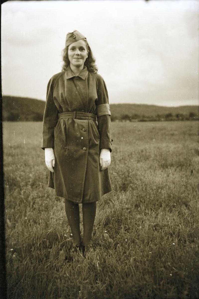 061d3a1d4697 Anna-Lisa i Hugalyckan står uniformsklädd ute på ett stort gräsfält. Hon  har en
