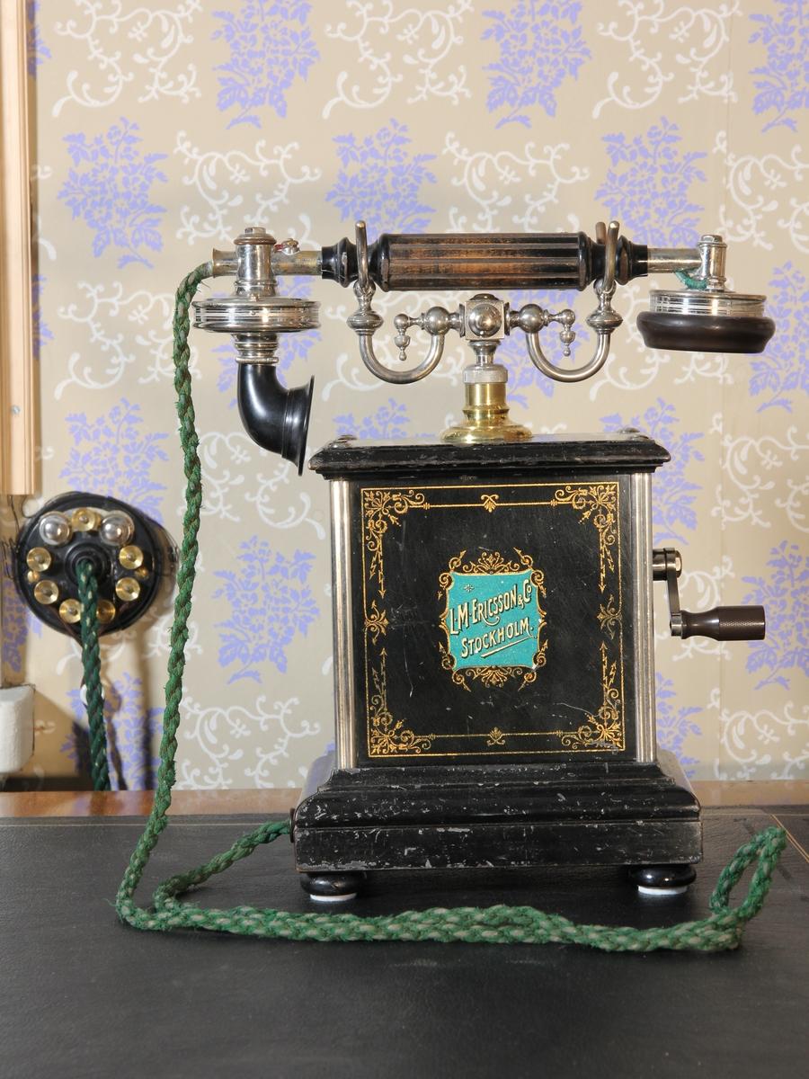 Telefon, bordsapparat med lur. Modell A 381 Jubileumsapparat (framtagen till L M Ericssons 25-årsjubileum 1901). Stående rektangulär med klyka av vitmetall. Svartmålad med dekor och text bland annat i guldfärg. Vev. Väggplint och grön sladd.