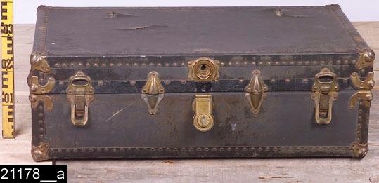 Anmärkningar: Koffert, omkring 1800.  Gångjärnsförsett platt lock. På kortsidorna finns bärhandtag av läder och på framsidan två låssnäppar samt ett lås. På koffertens framsida sitter ett fabriksmärke (bild 21178__e). Utvändigt är samtliga hörn och kanter försedda med beslag. Invändigt två olika insatser (bild 21178__b-d). H:310 L:950 Dj:550  Tillstånd: Skadad och sliten både utvändigt och invändigt. Nyckel saknas.  Historik: Gåva från Margit Rabe, Västerås. Ursprunglig ägare var Anselm Rabe, Västerås.