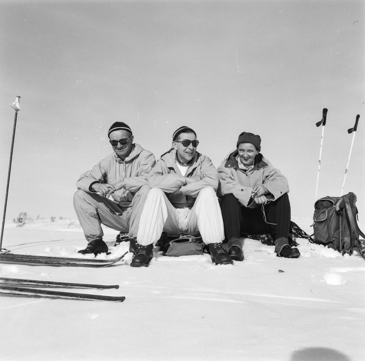 Vinter og snø to menn og ei kvinne på skitur, anorakkar, strekkbukser, beksaumsko, solbriller, ski og stavar, Kongsberghue, panneband, ryggsekk, ransel,