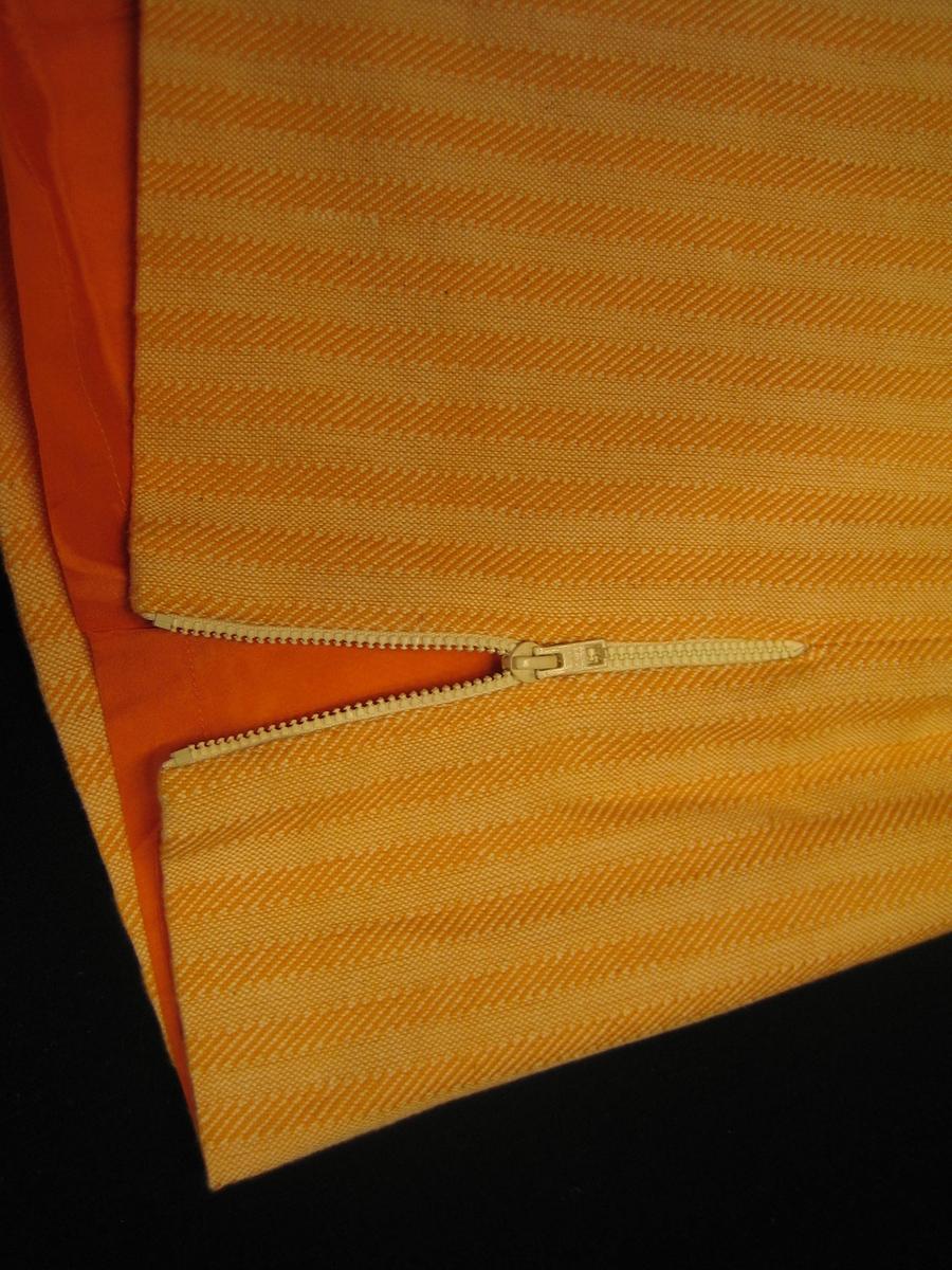 Orangegul sidenfodrad rak kjol i bomull. Tyget är vävt i kypert och tuskaft i 10 mm breda ränder. Kjolen har två sprängveck bak och dragkedja i vänster sida och en 25 mm bred linning med knapp och knapphål. Kjolen är försedd med ett sprund med dragkedja i vänster sida.