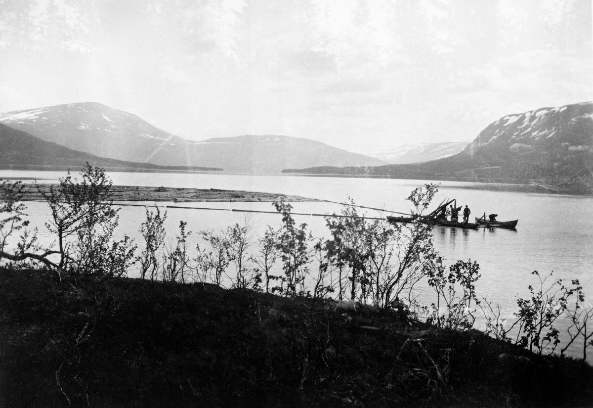 Spillflåtefløting over Unkervatn i Hattfjelldal.  Fotografiet er tatt fra en bakkekam med buskvegetasjon, som dessverre delvis skjuler spillflåten.  På flåten ser det ut til å være tre mann, og en mann står i en båt ved siden av.  Bak flåten ligger en annen robåt.  Der finnes også en tømmerbom med løstømmer som skal trekkes cirka ei mil over vatnet.  I bakgrunnen høye fjell med snøflekker.