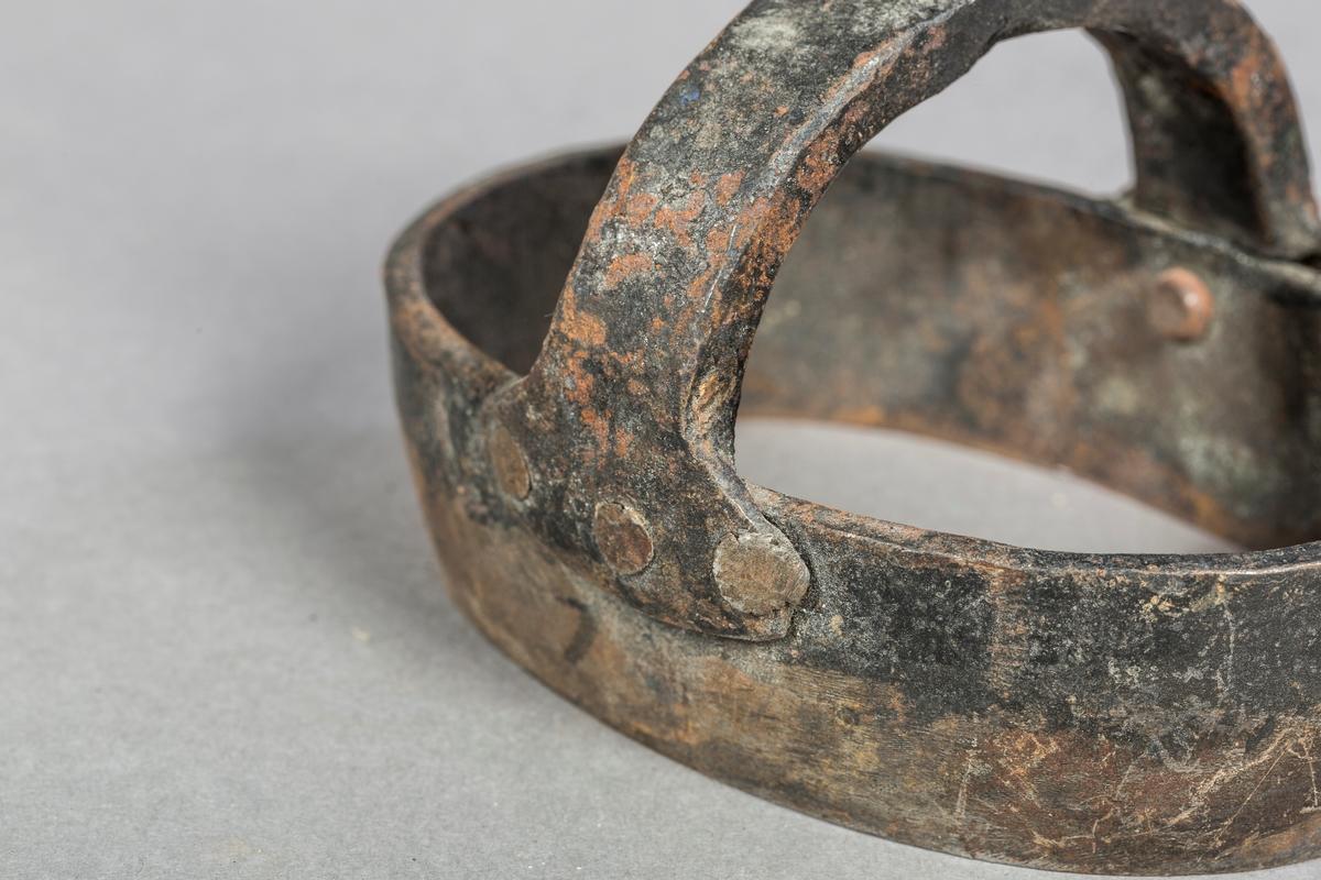 Ovalt jern med fastnaglet håndtak på bue på oversiden.