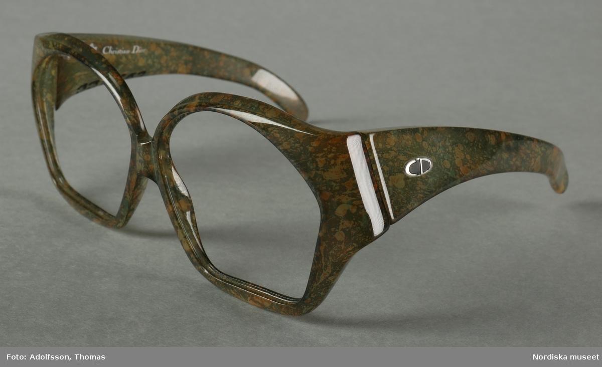 """Solglasögonbågar av optylplast. Oregelbundet formade bågar. Bågarna är mörkgröna med bruna detaljer i en marmoreringseffekt. Små näskuddar inbyggt i bågen (som en saddelbrygga). Metallgångjärn. Skalmarna är breda vid gångjärnen med """"CD""""-monogrammet på utsidan i silver. På vänstra skalmens insida står det """"MADE IN GERMANY 2028-80"""", på högra skalmens insida står det """"Optyl Christian Dior"""".  /Petrine Knight, 2014-10-29"""
