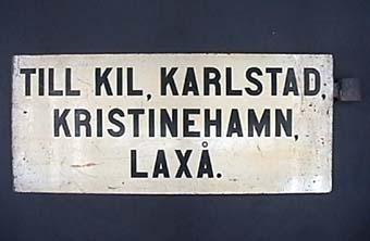 """Dubbelsidig plåtskylt med svart text på gulvit botten: """"TILL KIL, KARLSTAD, KRISTINEHAMN, LAXÅ.""""  Samma text på andra sidan."""