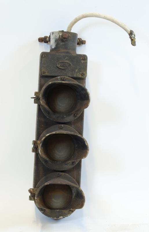"""Plattformssignal, hängande uppifrån med tre sken i höjdled. Ovanför lamporna sitter ett lock med """"AGA"""" ingjutet. Skärmarna är gjutna av aluminium och fastskruvade i hållare med glaset emellan. Hållarna sitter fast med gångjärn på höger sida och har vingmuttrar på vänster sida. Plattformssignalen hängs i överkant och spännes fast med tre skruvar. I överkanten sitter en avklippt sladd. Signalen är målad med svart färg."""