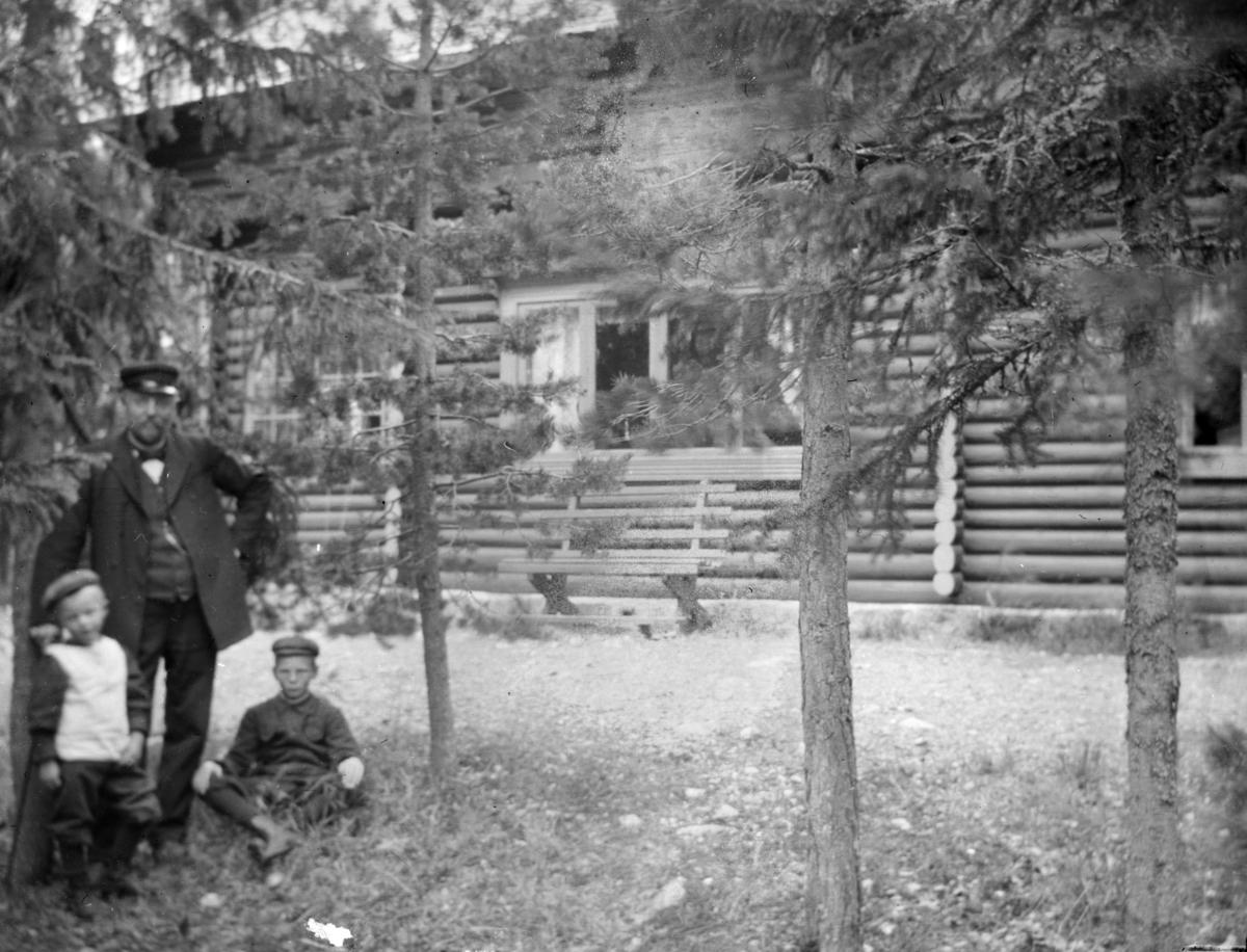 Mann med to barn og tømmerhus i bakgrunnen