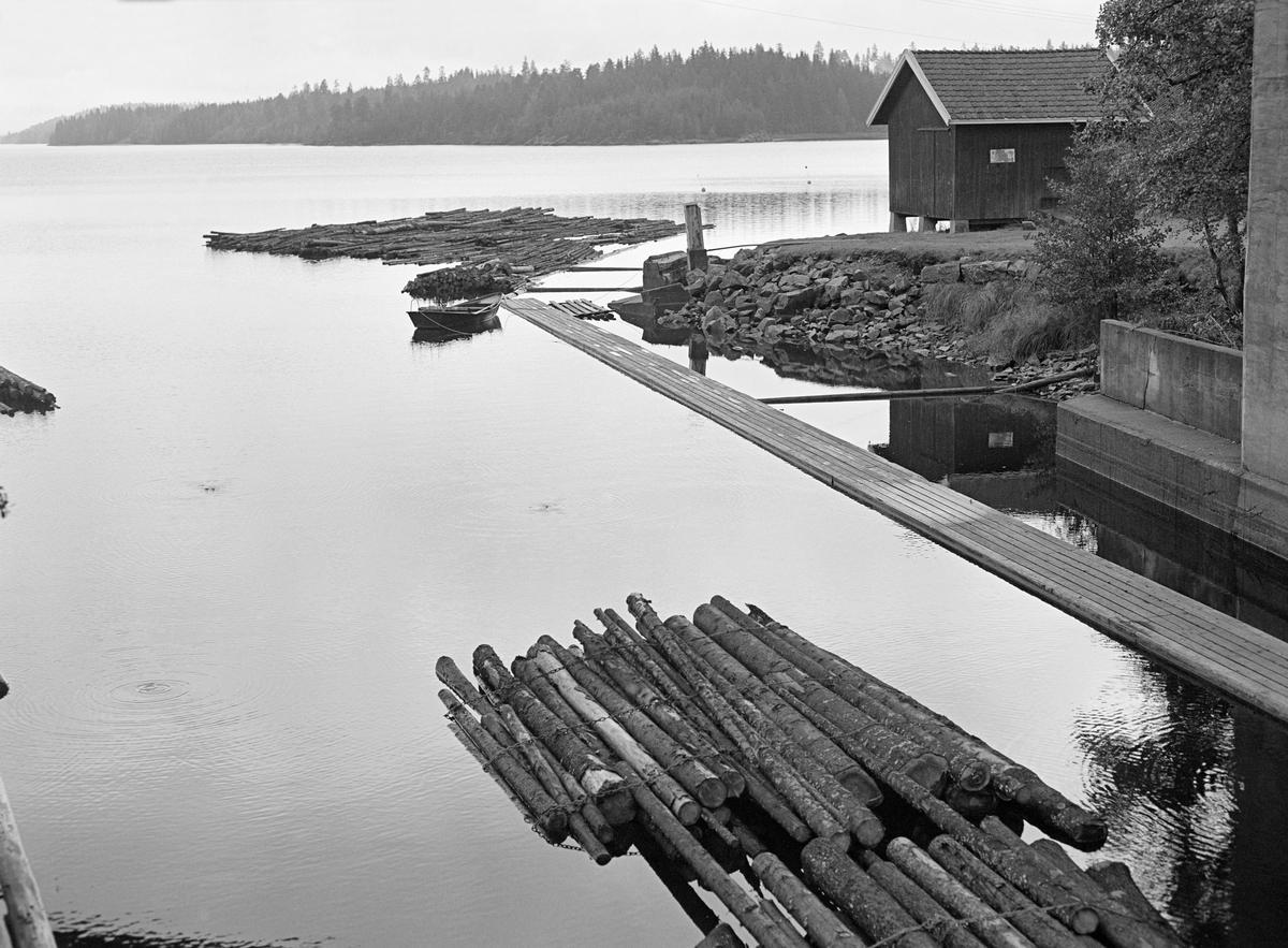 Fra østre side av innløpet til Ørje sluser i sørenden av Rødenessjøen i Marker kommune i Østfold.  Fotografiet er tatt høsten 1982, det siste året det foregikk tømmerfløting i Haldenvassdraget.  I denne fasen ble det bare fløtet ubarket massevirke (papirråstoff) i tre meters lengder til Saugbrugsforeningen.  Tømmeret ble utislått buntevis fra lastebiler ved Skulerud i Høland.  Derfra ble det buksert i store slep sørover mot det stedet der dette fotografiet er tatt.  Her måtte slepet deles opp i kortere lenker som fikk plass i de tre slusekamrene som skulle ta det trygt 10 høydemeter ned til Ørjeelva og den nedenforliggende Øymarksjøen.  Med dette tømmersortimentet gikk det fire bunter – «moser» – i hver slusevending.  Vi ser den bakre enden av ei slik slusevending på vannspeilet i forgrunnen.  Langs den østre kanalbredden lå det en gangbane av planker, som fløterne kunne gå på.   Ved enden av denne lå det en båt.  Bak denne igjen ser vi en lensearm, der den gjenværende delen av et slep som skulle deles opp i mindre sluseenheter lå fortøyd.  Inne på land, ved enden av gangbanen, var det et tappeskap for diesel til Haldenvassdragets Fellesfløtningsforenings varpebåter.  Bygningen til høyre var et lagerhus som Haldenvassdragets Kanalselskap eide.  En liten historikk om tømmerfløting og kanaliseringsarbeid i Haldenvassdraget finnes under fanen «Opplysninger».
