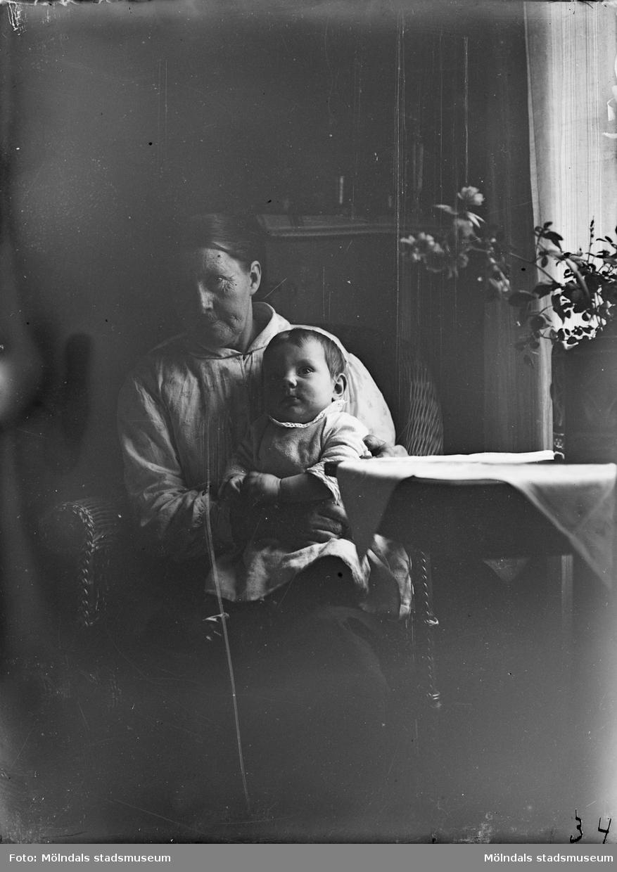 I hemmiljö där en äldre kvinna sitter med ett litet barn i knäet, troligtvis 1920-30-tal.
