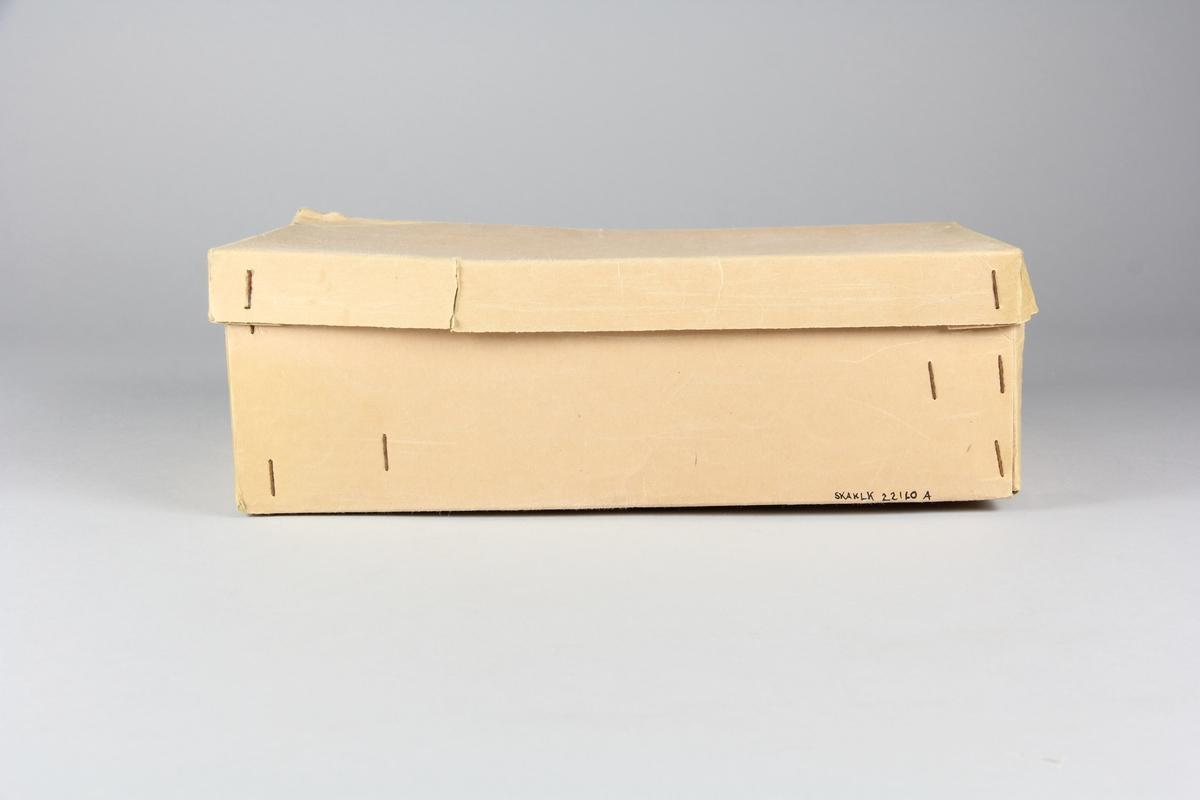 """Skokartong med lock och skyddande silkespapper. Kartong av gulnat papper som hålls ihop av något rostiga häftklamrar. Locket trasigt på några ställen längs kantet och ihoptejpat med transparent plasttejp. Utsidan av lådans ena kortsida pryds av ett tryck i två färger. Brun text runt en rosa oval med en loggotype. Stämplat på lådan står information om skorna. över den rosa ovalen sitter en prislapp av papper med loggotypen för """"Rättviks skoaffär"""" trykt högst upp. I lådan ligger ett ark brunt dubbelt silkespapper med mjukt mellanlägg med ihop kreppade kanter. Pappret pryds av tre loggotyper för Guide-step funktionssko och längs ena kanten """"PATENT S. Örebro litho"""". A: kartong B: lock C: silkespapper"""