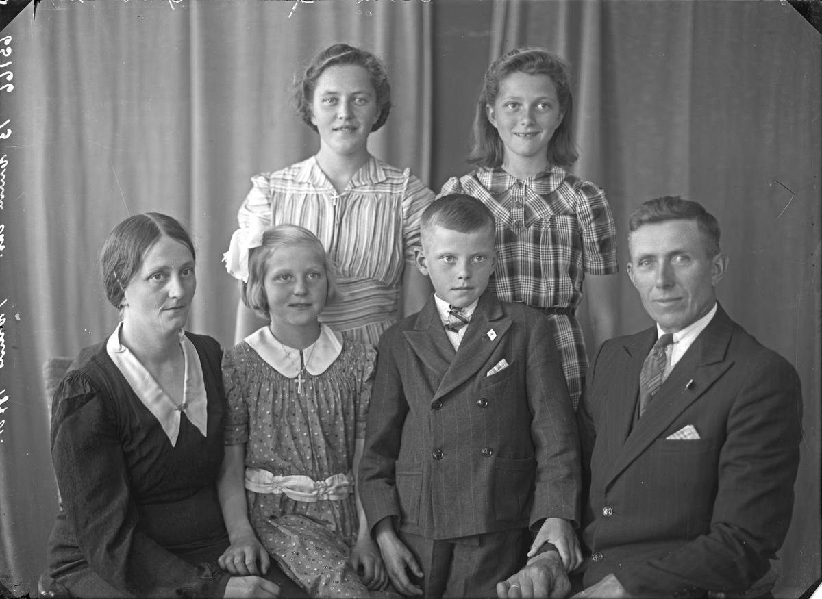 Portrett. Familiegruppe på seks. Mor, far, 3 unge piker og en ung gutt. Bestilt av John Evje. Tysværvåg.
