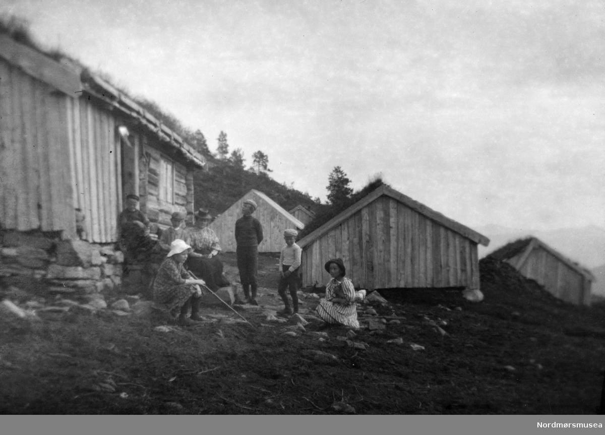 Flokk barn og noen voksne utenfor et hytte-tun? Muligens fra et museum? Det er usikkert hvor bildet er tatt. De vi ser på bildet er trolig fra Sverdrupfamilien. Fra Sverdrupsamlingen ved Nordmøre museums fotosamlinger.