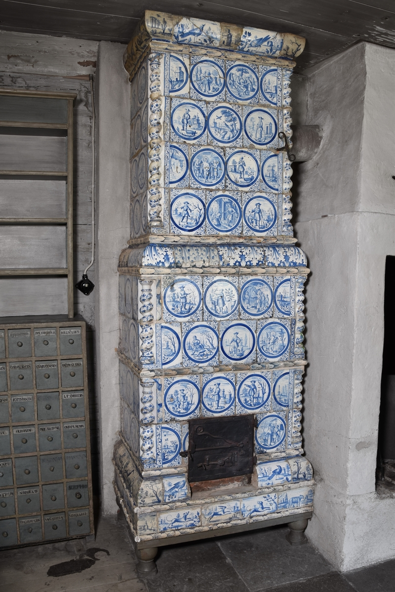 Kakelugn, flat med något indragen och avsmalnande överdel. Vitglaserade kakel från olika kakelugnar med blå dekor i form av figurmotiv i huvudsakligen rundlar. Spiralvridna hörnkolonetter. Rak avslutning upptill. Fotställning av järn. Delar av kakelugnen tillvaratagen 1903 i Rinkeby, Spånga, Stockholms län. Troligen består kakelugnen även av delar från kakelugn som fanns i huset vid rivningen.  Kakelugnslucka från annan kakelugn (SKANM.0149593). Kakel från kakelugn  NM 96737 och NM 96738 samt omärkt kakelugn från ursprunglig plats.