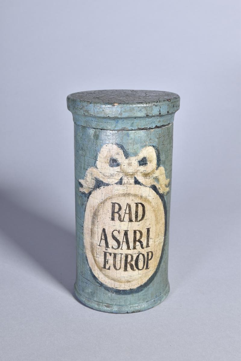 Apotekskärl, ståndkärl, av grönmålat trä, cylindriskt med plant lock. Svart text inom oval med bandrosett.