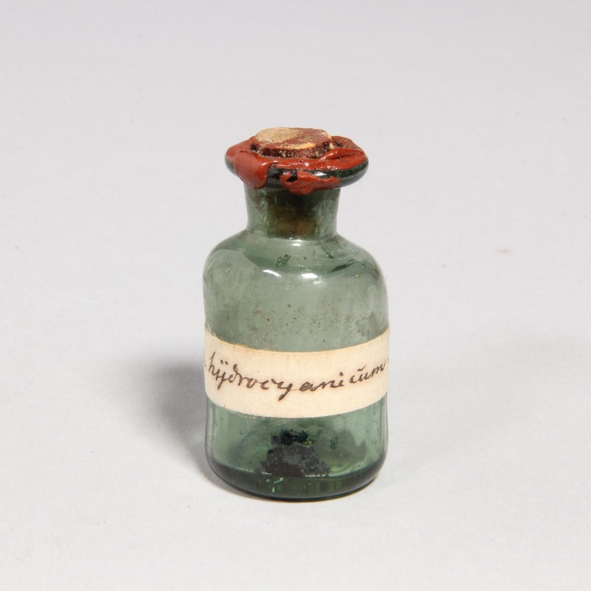 Flaskor, 10 st, av grönt glas med proppar av kork förseglade med rött lack. Står i pappask med lock klädd med marmorerat papper. Flaskorna innehåller rester av cyanid.