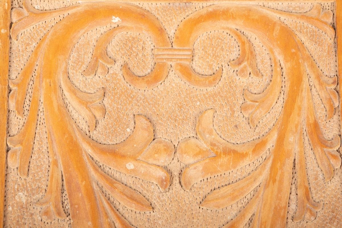 Lokk laget av tre. Lokket har utskåret dekor av akantus. Den ene kanten på lokket er løs.