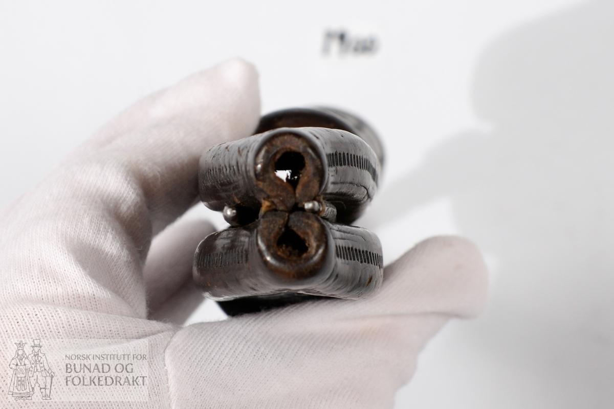 """Kniv, tvislir. Samansett av to lerslirer, initialene HSS.  Årstalet 1735. Dekor på båe slirene.  Treskaft av bjørk, godt brukte blad av jern.  Sylvholkar. Kvivane og slira er av ulik alder, og knivane ser ut til å ha kome til etter kvart. Kanskje 100 år yngre. Det eine knivskaftet er litt grøvre enn det andre. Knivslirene er sett samman av ein gaffel - liknande stav. Slirene er laga med firkanta smettestolar som """"gaffelen"""" blir stukke ned gjennom, og som låser slirene saman. Gaffelen er av jern, og påsett toppfeste i messing til oppfesting i belte. Denne svingar laust rundt i jern - gaffelen. Leret har skore dekor. Sylvholkene på båe knivane har gravert dekor."""